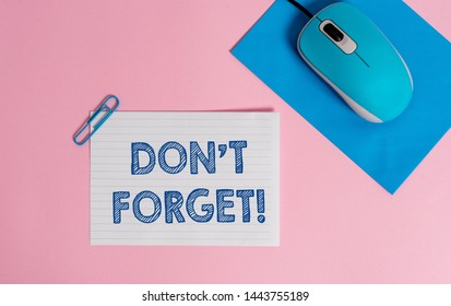 Text sign showing Don T Forget. Conceptual photo used to remind someone about an important fact or detail Wire electronic mouse striped blank paper sheets clip colored background.