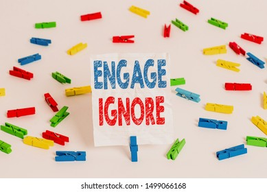 Text sign showing Engage Ignore. Conceptual photo Silent Treatment Manipulative Punishment Sulking Shunning Colored clothespin papers empty reminder white floor background office.