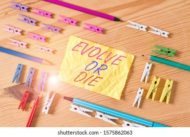 Text sign showing Evolve Or Die. Conceptual photo Necessity of change grow adapt to continue living Survival Colored clothespin papers empty reminder wooden floor background office.