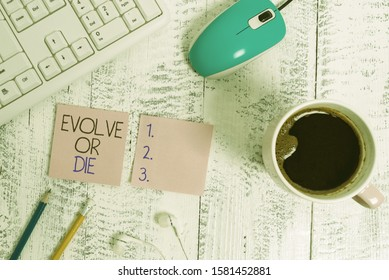 Text sign showing Evolve Or Die. Conceptual photo Necessity of change grow adapt to continue living Survival technological devices colored reminder paper office supplies keyboard mouse.