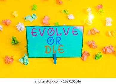 Text sign showing Evolve Or Die. Conceptual photo Necessity of change grow adapt to continue living Survival Colored crumpled papers empty reminder white floor background clothespin.