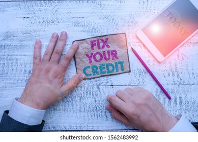 Text sign showing Fix Your Credit. Conceptual photo Keep balances low on credit cards and other credit Hand hold note paper near writing equipment and modern smartphone device.