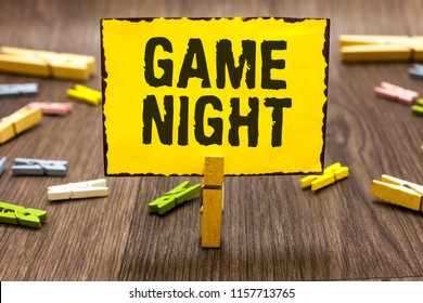 Text sign showing Game Night. Conceptual photo event in which folks get together for the purpose of getting laid Clothespin holding yellow paper note several clothespins wooden floor.