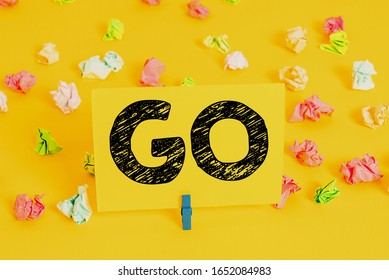 Text sign showing Go. Conceptual photo to move or travel somewhere in order to do something Leave or depart Colored crumpled papers empty reminder white floor background clothespin.
