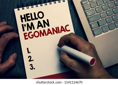 Text sign showing Hello I am An Egomaniac. Conceptual photo Selfish Egocentric Narcissist Self-centered Ego Written words and number on notepad man hold marker keyboard on wooden desk.