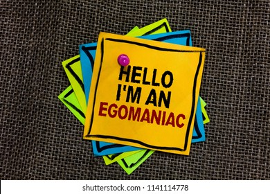 Text sign showing Hello I am An Egomaniac. Conceptual photo Selfish Egocentric Narcissist Self-centered Ego Black bordered different color sticky note stick together with pin on jute sack.