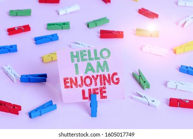 Text sign showing Hello I Am Enjoying Life. Conceptual photo Happy relaxed lifestyle Enjoy simple things Colored clothespin papers empty reminder pink floor background office pin.
