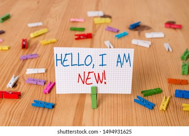 Text sign showing Hello I Am New. Conceptual photo used as greeting or to begin telephone conversation Colored clothespin papers empty reminder wooden floor background office.