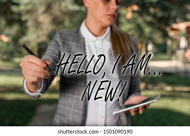 Text sign showing Hello I Am New. Conceptual photo used greeting or begin telephone conversation Outdoor background with business woman holding lap top and pen.