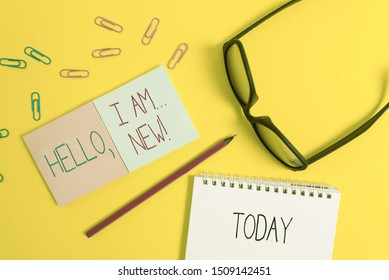 Text sign showing Hello I Am New. Conceptual photo used greeting or begin telephone conversation Square blank sticky notepads pencil clips eyeglasses yolk color background.