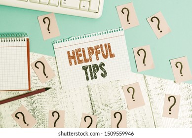 Text sign showing Helpful Tips. Conceptual photo Useful secret Information Advice given to accomplish something Writing tools, computer stuff and math book sheet on top of wooden table.