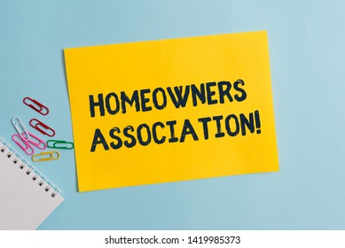 Text sign showing Homeowners Association. Conceptual photo Organization with fee for upkeeps of Gated Community Plain cardboard and writing equipment placed above pastel colour backdrop.