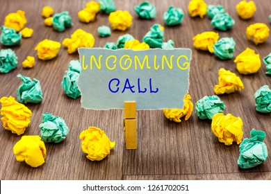 Text sign showing Incoming Call. Conceptual photo Inbound Received Caller ID Telephone Voicemail Vidcall Clothespin holding gray note paper crumpled papers several tries mistakes.