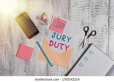 Text sign showing Jury Duty. Conceptual photo obligation or a period of acting as a member of a jury in court Envelope sheet smartphone notes pen notepad clips scissors wooden back.
