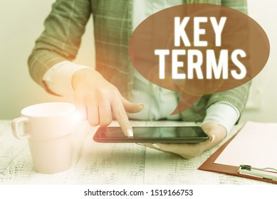 Text sign showing Key Terms. Conceptual photo Words that can help a demonstrating in searching information they need Business woman sitting with mobile phone and cup of coffee on the table.