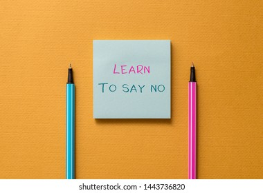 Text sign showing Learn To Say No. Conceptual photo decline or refuse few things before you destroy yourself Front view blank colored sticky note two ballpoints cool yolk background.
