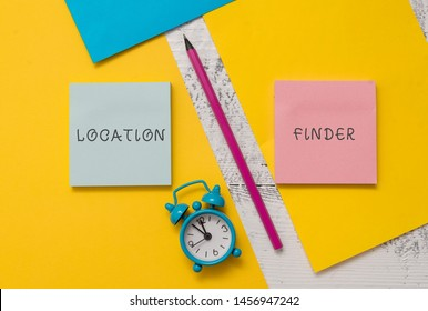 Text sign showing Location Finder. Conceptual photo A service featured to find the address of a selected place Notepads marker pen colored paper sheets alarm clock wooden background.