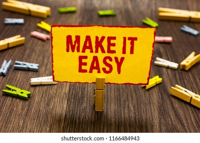 Text sign showing Make It Easy. Conceptual photo Smart approach Effortless Free from worries or difficulties Clothespin holding yellow paper note several clothespins wooden floor.