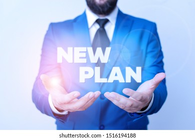 Text sign showing New Plan. Conceptual photo Start of a detailed proposal of doing or achieving something Man with opened hands in fron of the table. Mobile phone and notes on the table.