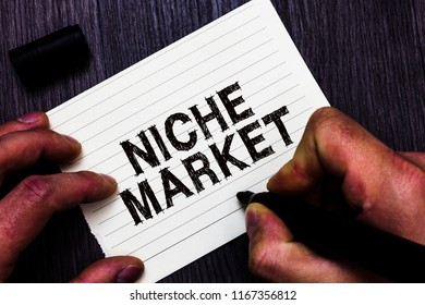 Text sign showing Niche Market. Conceptual photo Subset of the market on which specific product is focused Man holding marker notebook page communicate ideas Wooden background.