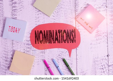 Text sign showing Nominations. Conceptual photo action of nominating or state being nominated for prize Ballpoints pens blank colored speech bubble sticky notes wooden background.