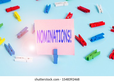 Text sign showing Nominations. Conceptual photo action of nominating or state being nominated for prize Colored clothespin papers empty reminder blue floor background office pin.