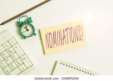 Text sign showing Nominations. Conceptual photo action of nominating or state being nominated for prize White pc keyboard with empty note paper and pencil above white background.