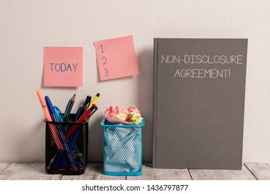 Text sign showing Non Disclosure Agreement. Conceptual photo Legal Contract Confidential Material or Information Stick Pad Notes on Wall Two Pencil Pots Hardcover Notebook on Work Desk.