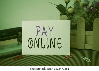 Text sign showing Pay Online. Conceptual photo buy products or service using credit card on any website Flowers and writing equipments plus plain sheet above textured backdrop.