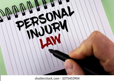 Text sign showing Personal Injury Law. Conceptual photo guarantee your rights in case of hazards or risks written by Man on Notepad holding Marker on the plain background.