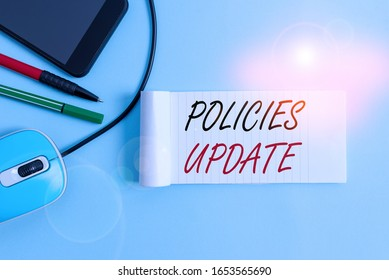 Text sign showing Policies Update. Conceptual photo act of adding new information or guidelines formulated Notebook and writing equipment with modern gadget above pastel backdrop.