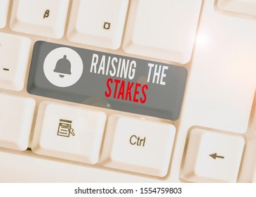 Text sign showing Raising The Stakes. Conceptual photo Increase the Bid or Value Outdo current bet or risk White pc keyboard with empty note paper above white background key copy space.