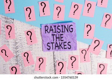 Text sign showing Raising The Stakes. Conceptual photo Increase the Bid or Value Outdo current bet or risk Scribbled and crumbling papers with thick cardboard above wooden table.