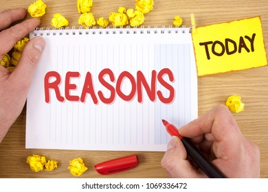 Text sign showing Reasons. Conceptual photo Causes Explanations Justifications for an action or event Motivation written by Man on Notepad holding  Marker on wooden background Today Paper Balls,