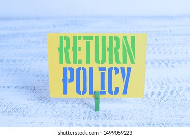 Text sign showing Return Policy. Conceptual photo Tax Reimbursement Retail Terms and Conditions on Purchase Green clothespin white wood background colored paper reminder office supply.