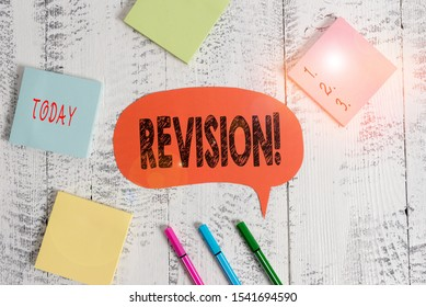 Text sign showing Revision. Conceptual photo action of revising over someone like auditing or accounting Ballpoints pens blank colored speech bubble sticky notes wooden background.