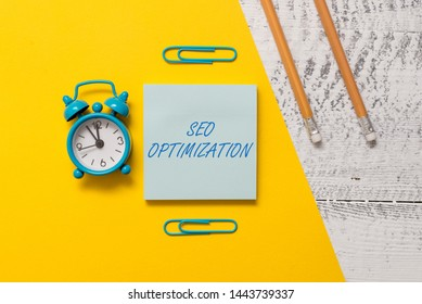 Text sign showing Seo Optimization. Conceptual photo process of affecting online visibility of website or page Notepad clips colored paper sheet markers alarm clock wooden background.