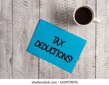 Text sign showing Tax Deductions. Conceptual photo reduction income that is able to be taxed of expenses Pastel Colour paper placed next to a cup of coffee above the wooden table.