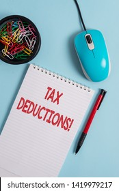 Text sign showing Tax Deductions. Conceptual photo reduction income that is able to be taxed of expenses Notebook and writing equipment with computer mouse above pastel backdrop.