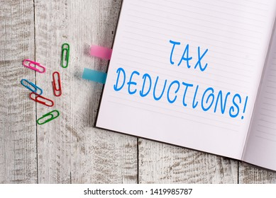 Text sign showing Tax Deductions. Conceptual photo reduction income that is able to be taxed of expenses Thick pages notebook stationary placed above classic look wooden backdrop.