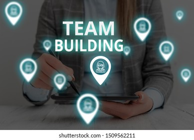 Text sign showing Team Building. Conceptual photo Types of activities used to enhance social relations Woman wear formal work suit presenting presentation using smart device.