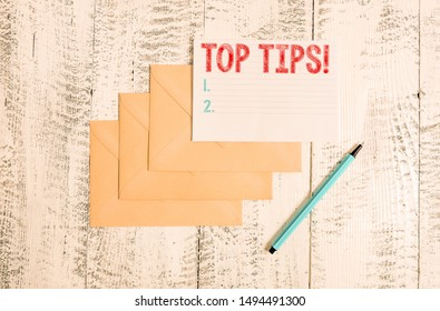 Text sign showing Top Tips. Conceptual photo small but particularly useful piece of practical advice Three envelopes marker ruled paper sheet old wooden vintage background.
