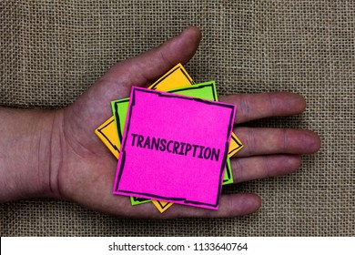 Text sign showing Transcription. Conceptual photo Written or printed process of transcribing words text voice Holding small pitches art papers thoughts ideas memories mat black shadow.