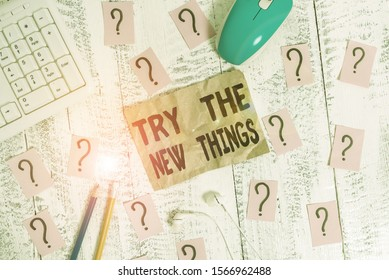 Text sign showing Try The New Things. Conceptual photo Breaks up Life Routine Learn some Innovative Skills Writing tools, computer stuff and scribbled paper on top of wooden table.