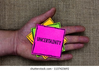 Text sign showing Uncertainty. Conceptual photo Unpredictability of certain situations events behavior Holding small pitches art papers thoughts ideas memories mat black shadow.