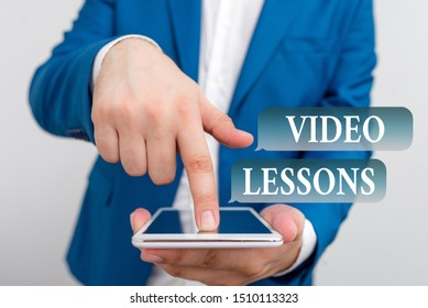 Text sign showing Video Lessons. Conceptual photo Online Education material for a topic Viewing and learning Businessman in the blue suite with lap top pointing with finger.