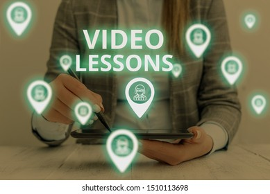 Text sign showing Video Lessons. Conceptual photo Online Education material for a topic Viewing and learning Woman wear formal work suit presenting presentation using smart device.