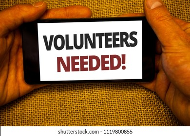 Text sign showing Volunteers Needed Motivational Call. Conceptual photo Social Community Charity Volunteerism Jute sack background hand holding iPhone with colorful alphabetic syllable.