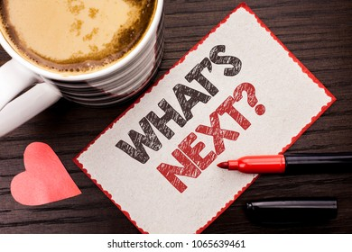 Text sign showing What s Next Question. Conceptual photo Asking Imagination Choice Solution Next Questionaire written on Sticky Note on the wooden background Coffee Cup Heart Marker next to it.