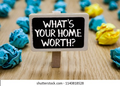 Text sign showing What s is Your Home Worth question. Conceptual photo Value of a house Property Cost Price Rate Paperclip hold written chalkboard behind paper lumps on woody deck.